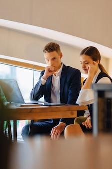 I giovani uomini d'affari ragazzo e ragazza lavorano con un computer portatile, una tavoletta e le note nel caffè