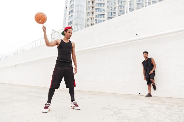 I giovani uomini sportivi africani concentrati giocano a pallacanestro