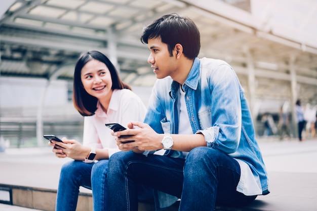 I giovani usano lo smartphone e sorridono mentre sono seduti nel tempo libero.