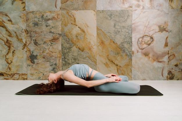 I giovani yogini che praticano matsyasana posano in leggins blu pastello e fuoco superiore e selettivo