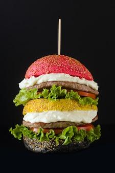 I grandi hamburger con diversi colori impanano i panini in rosso, giallo e nero con crema di parmigiano e pomodori, insalata sul tavolo.