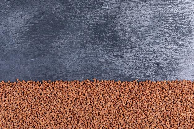 I grani di grano saraceno distesi su uno spazio libero strutturato grigio scuro per il testo