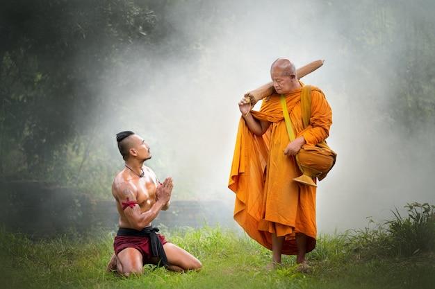 I guerrieri antichi tailandesi pagano il rispetto al monaco buddista anziano nella foresta