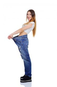 I jeans della ragazza graziosa di grandi dimensioni godono di una figura snella. perdita di peso. ragazza esile in un raccordo largo su uno sfondo bianco