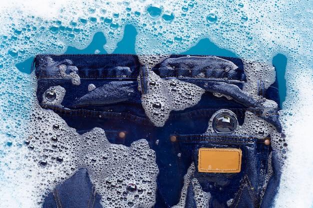I jeans sono immersi nella dissoluzione dell'acqua detergente in polvere. concetto di lavanderia