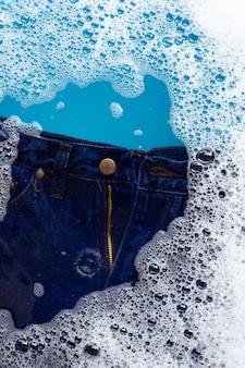 I jeans vengono immersi in soluzione di acqua detergente in polvere. concetto di lavanderia