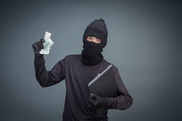 I ladri maschi rubano un computer portatile su gray