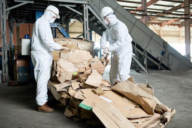 I lavoratori di hazmat si occupano dell'ordinamento del cartone nella moderna fabbrica