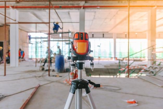I lavoratori edili effettuano le misurazioni con lo strumento a livello laser in una nicchia per i radiatori