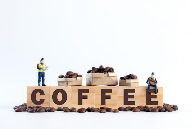 I lavoratori in miniatura stanno controllando i prodotti e trasportano i chicchi di caffè su blocchi di alfabeto in legno con la lettera caffè