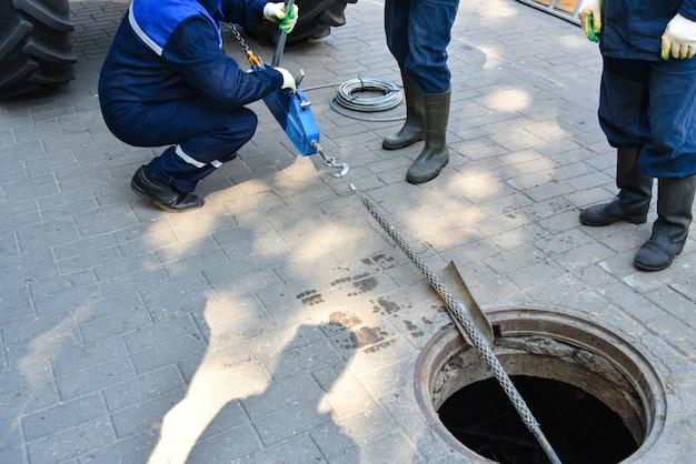 I lavoratori smantellano il cavo di telecomunicazione nel pozzo