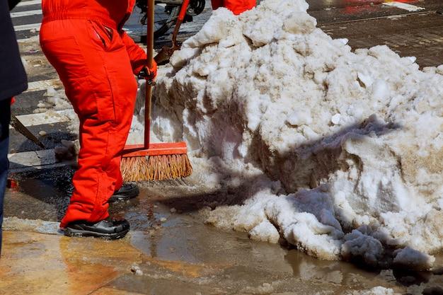 I lavoratori spazzano la neve dalla strada in inverno. pulizia della strada dalla tempesta di neve