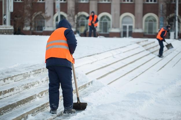 I lavoratori spazzano neve dalla strada in inverno, pulizia strada dalla tempesta di neve.