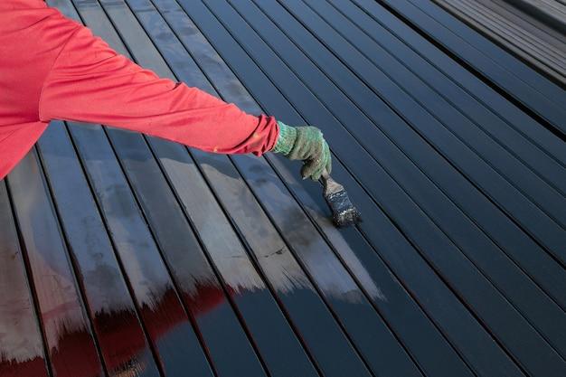 I lavoratori stanno dipingendo pavimenti in acciaio.