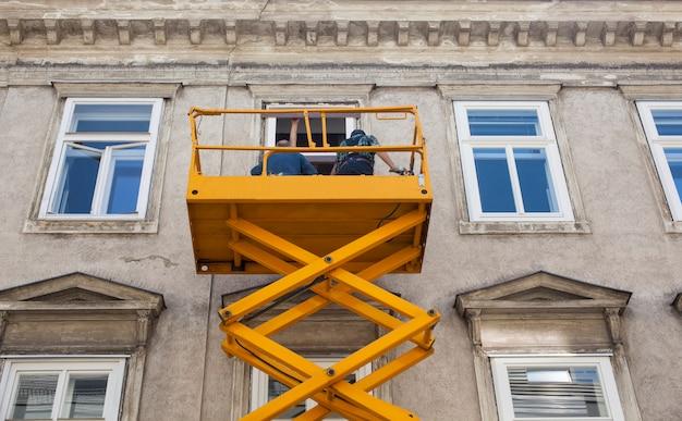 I lavoratori su un raccoglitore di ciliegie ristrutturano la facciata di un edificio