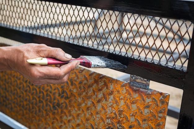 I lavoratori usano i pennelli in acciaio nero.