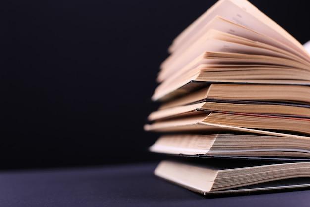 I libri aperti sono impilati sullo scrittorio sul nero, isolato. compiti difficili a scuola, una montagna di conoscenza.