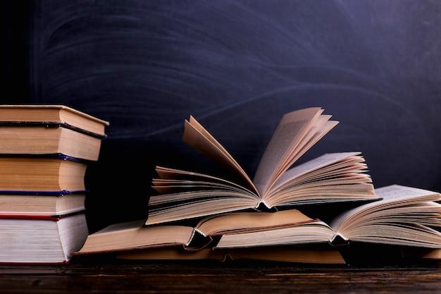 I libri aperti sono una pila sulla scrivania, sullo sfondo di una lavagna