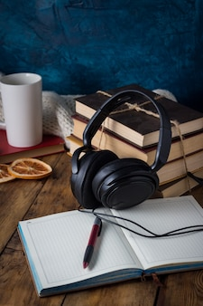 I libri sono impilati, cuffie, tazza bianca, fette d'arancia, diario aperto su un legno. concetto di libri audio