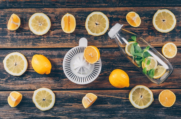 I limoni con gli spremiagrumi e la bottiglia di vetro piatti giacciono su uno sfondo di legno scuro