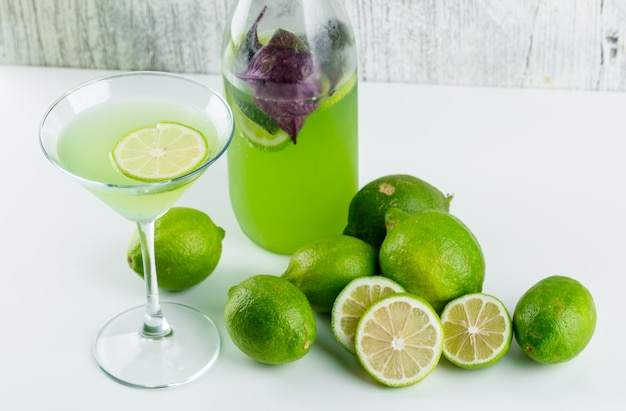 I limoni con limonata, foglie del basilico su bianco e grungy, vista dell'angolo alto.