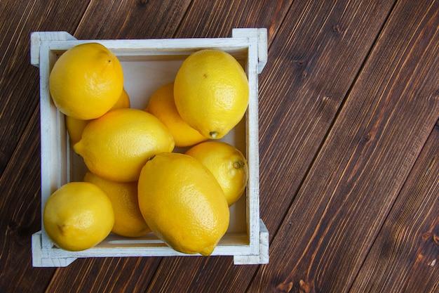 I limoni in un piano della scatola di legno giacciono su un tavolo di legno