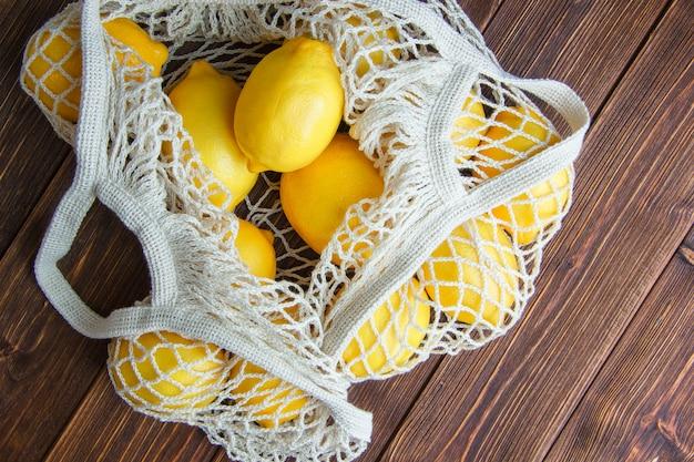 I limoni in un sacchetto di maglia piatta giacevano su un tavolo di legno