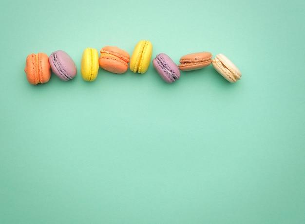 I macarons cotti multicolori rotondi con crema si trovano in una linea su un verde