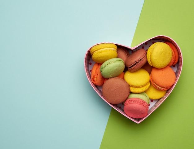 I macarons multicolori rotondi al forno si trovano in una scatola di cartone rossa a forma di cuore