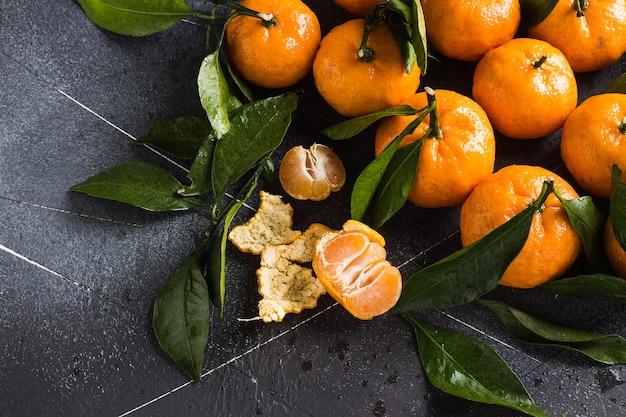 I mandarini con le foglie verdi si chiudono su su buio