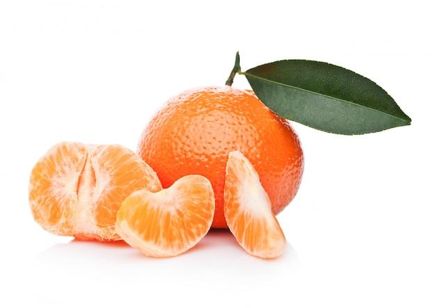 I mandarini organici freschi mandarini fruttifica con le foglie con le metà sbucciate su fondo bianco