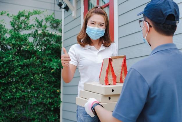 I maschi asiatici indossano maschere protettive e guanti medici per l'alimentazione portatile. servizio di consegna a domicilio in condizioni di quarantena dell'epidemia di malattia coronarica-19