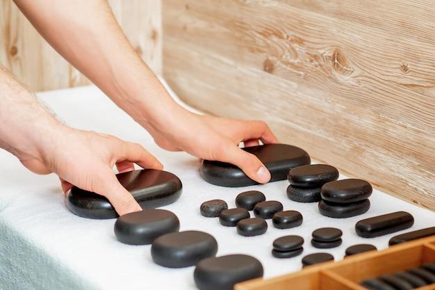 I massaggiatori stanno prendendo pietre calde nere per massaggi.