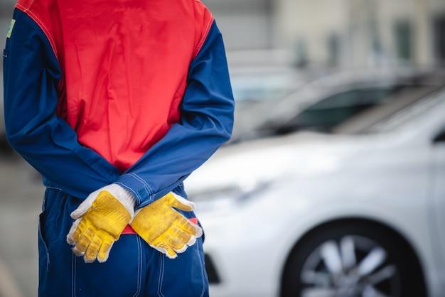 I meccanici asiatici indossano le tute da corsa per tornare nelle officine e nei centri di riparazione auto.