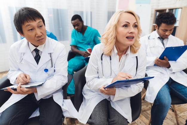 I medici sono seduti in una conferenza di dottorato.
