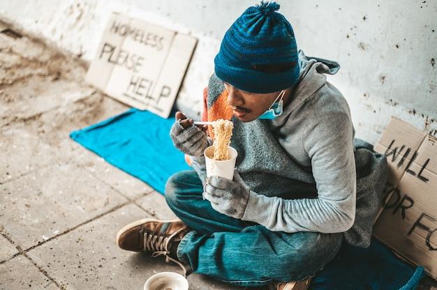 I mendicanti sedevano avvolti in panni e mangiavano noodles.