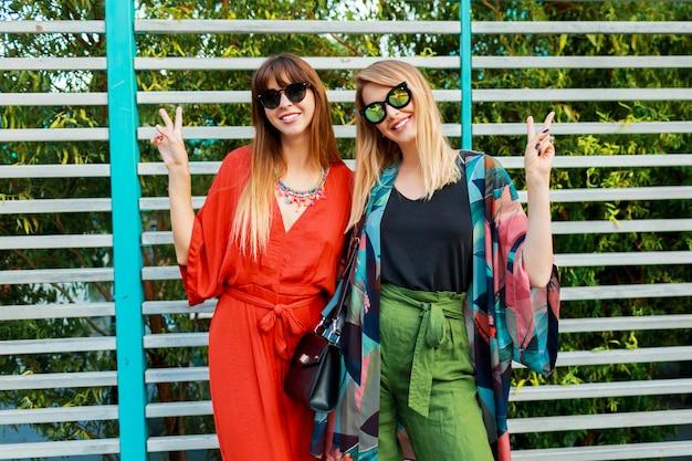 I migliori amici che si divertono insieme e godono le vacanze nella soleggiata città moderna