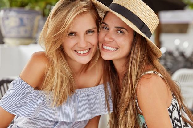 I migliori amici femminili felici si siedono al ristorante all'aperto