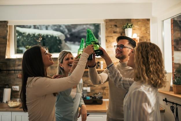 I migliori amici hanno alzato le braccia con bottiglie di birra che festeggiavano a casa la sera.