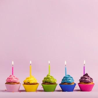 I muffin variopinti con le candele accese in una fila con spruzza sul contesto rosa