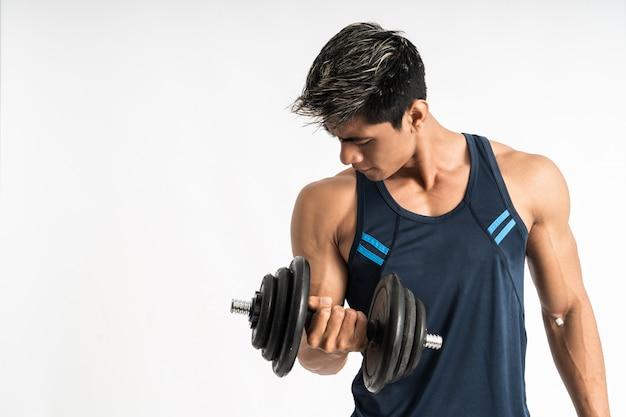 I muscoli dell'uomo asiatico sollevano pesi con manubri con energia nei bicipiti