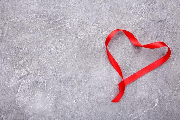 I nastri hanno modellato come cuori su calcestruzzo grigio, concetto del giorno di biglietti di s. valentino