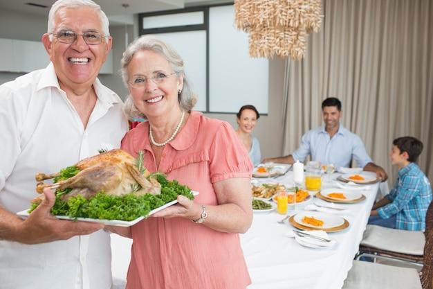 I nonni tenendo pollo arrosto con la famiglia al tavolo da pranzo