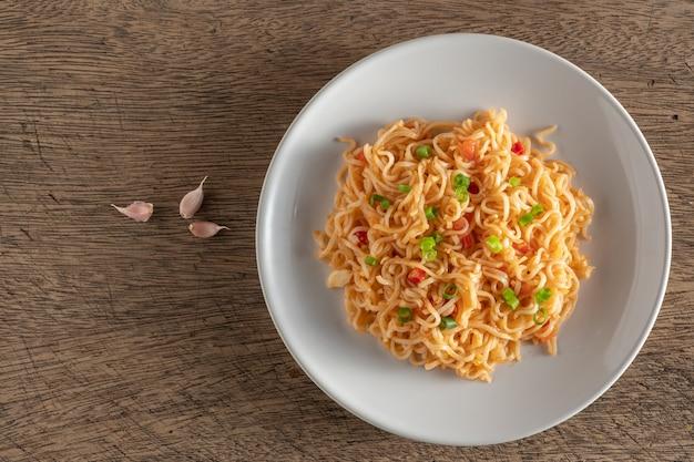 I noodles sono in un piatto bianco rotondo posizionato su un tavolo di legno. copi lo spazio