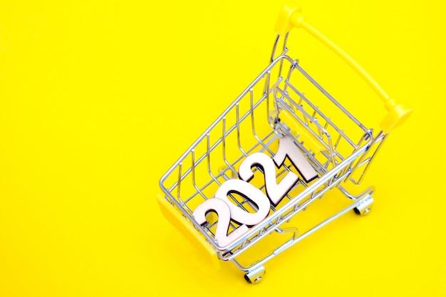 I numeri 2021 in un carrello giocattolo supermercato su uno sfondo giallo.
