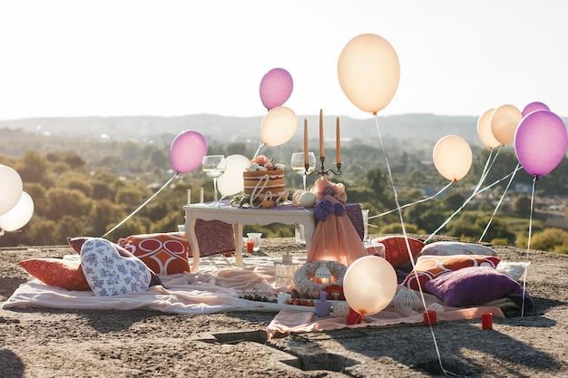 I palloncini levitano nell'aria sopra il tavolo bianco con le candele