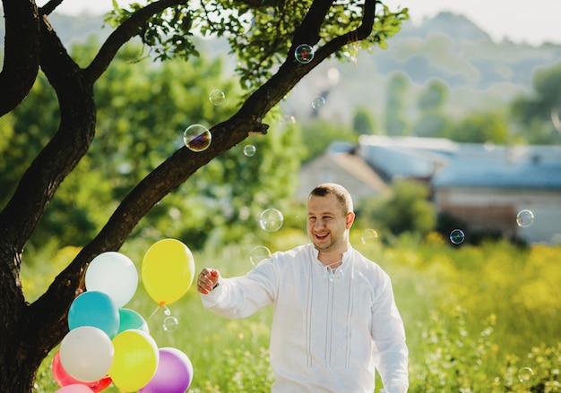 I palloni del sapone volano intorno ad un uomo che sta sotto l'albero verde