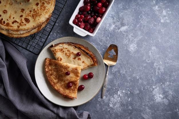 I pancake casalinghi tradizionali con i mirtilli rossi sono servito sulla tavola di pietra grigia copi lo spazio vista superiore.