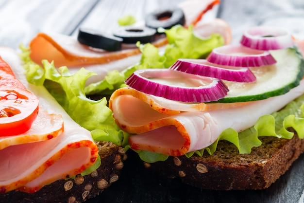 I panini con i pomodori tagliano le olive e il primo piano della cipolla rossa