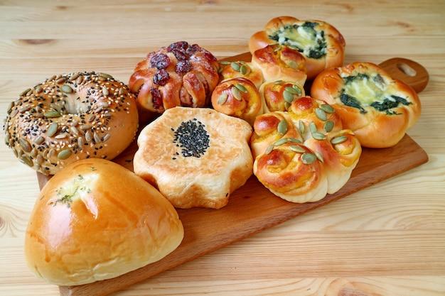 I panini e le pasticcerie assortiti sul vassoio di legno sono servito sulla tavola di legno